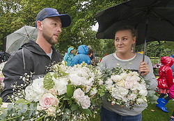 March 17, 2019 - Christchurch, Canterbury, New Zealand - Nicole and Mike Davies, who were married here Friday -- the same day a gunman killed at least 50 people and wounded dozens more -- bring their wedding flowers to place at a memorial at the Botanic Gardens. Mike Davies says he knew one of the people wounded; that person's 4-year-old daughter was also wounded and flown to Starship Hospital in Auckland. (Credit Image: © PJ Heller/ZUMA Wire)