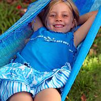 Young girl enjoying summertime swinging in a hammock.