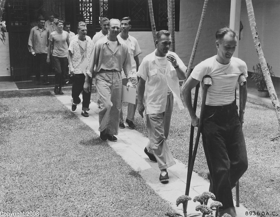 """HQ, Feaf, Tokyo -- Eleven happy U.S. Air Force men, who were shot down in their B-29 """"Superfort"""" during a leaflet dropping mission over North Korea in January 1953, walk through the courtyard of the Jockey Club in Hongkong, where warm showers, a steak dinner and new clothes awaited them. They are shown here in their """"prison"""" clothes. A short time later they were decked out in new U.S. Air Force uniforms that fit. A suitcase labeled with each man's name, was waiting on his bunk, containing both military and casual clothing, toilet, articles, pajamas, underwear and other necessities. 6 August 1955."""