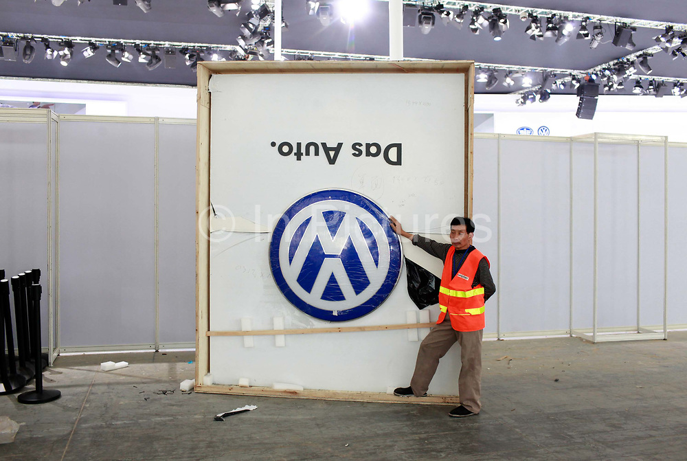 A worker stands by a Volkswagen AG logo while preparing the set for the China ( Guangzhou) International Automobile Exhibition in Guangzhou, Guangdong Province, China, on Monday, Nov. 21, 2011. Despite signs of slowing, China remains the largest and fastest growing market for international car makers, especially in the luxury sector.