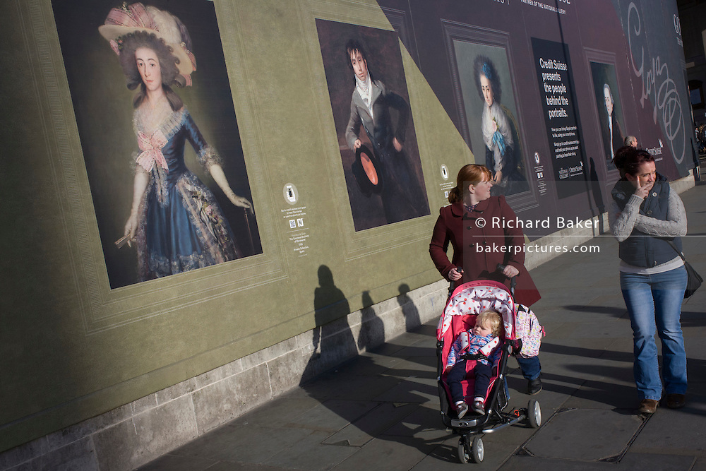 A mother and child pass Goya portraits in Trafalgar Square, central London