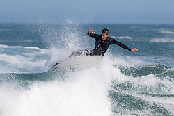 © Licensed to London News Pictures. 25/05/2020. Newquay, UK. A surfer catches a wave near Newquay, Cornwall. There is currently no RNLI Lifeguard service in the county due to Coronavirus (Covid-19). The county has experienced unusual combination of large swell and warm weather during the bank holiday weekend. Photo credit : Tom Nicholson/LNP