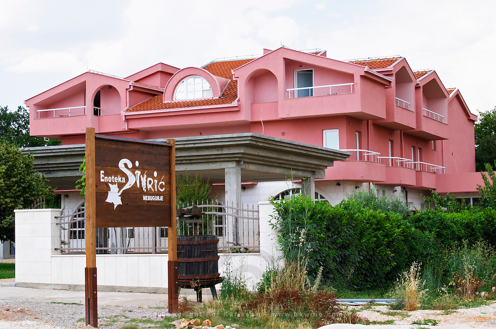 The winery, restaurant and auberge building with a sign and an old wine press as advertisement. Podrum Vinoteka Sivric winery, Citluk, near Mostar. Federation Bosne i Hercegovine. Bosnia Herzegovina, Europe.