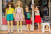 05 APRIL 2012 - HANOI, VIETNAM:   The daughter of a shop owner plays next to mannequins of children at a children's clothing shop in Hanoi, the capital of Vietnam.   PHOTO BY JACK KURTZ