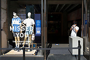As the UK's Coronavirus lockdown continues to ease, retailers re-open their doors to shoppers, an employee of a Levis shop on Regent Street awaits customers with hand sanitiser dispensers, and a sticky stencil lettering tells customers that they've been missed, on 18th June 2020, in London, England.