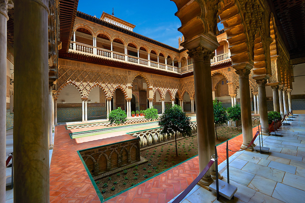 Patio de las Doncellas (Courtyard of the Maidens) an Italian Renaissance courtyard (1540-72) with Arabesque Mudéjar style plaster work, Alcazar of Seville, Seville, Spain . The Royal Alcázars of Seville (al-Qasr al-Muriq ) or Alcázar of Seville, is a royal palace in Seville, Spain. It was built by Castilian Christians on the site of an Abbadid Muslim alcazar, or residential fortress.The fortress was destroyed after the Christian conquest of Seville The palace is a preeminent example of Mudéjar architecture in the Iberian Peninsula but features Gothic, Renaissance and Romanesque design elements from previous stages of construction. The upper storeys of the Alcázar are still occupied by the royal family when they are in Seville. <br /> <br /> Visit our SPAIN HISTORIC PLACES PHOTO COLLECTIONS for more photos to download or buy as wall art prints https://funkystock.photoshelter.com/gallery-collection/Pictures-Images-of-Spain-Spanish-Historical-Archaeology-Sites-Museum-Antiquities/C0000EUVhLC3Nbgw <br /> .<br /> Visit our MEDIEVAL PHOTO COLLECTIONS for more   photos  to download or buy as prints https://funkystock.photoshelter.com/gallery-collection/Medieval-Middle-Ages-Historic-Places-Arcaeological-Sites-Pictures-Images-of/C0000B5ZA54_WD0s