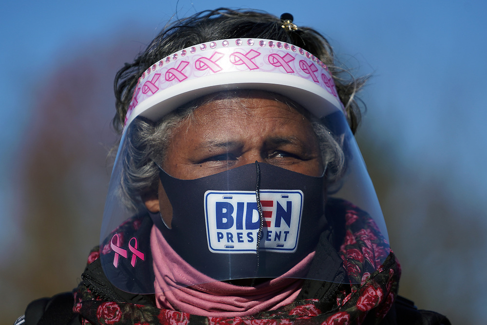 Biden supporter Pat Wheeler-Gibson, of Easton, wears a mask and face shield as she stands across from Dutch Springs, where Sen. Kamala Harris is appearing Nov. 2, 2020, for a drive-in rally in Bethlehem Township, Pennsylvania.