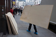 Delivery man carries the last sheet of plyboard for local construction project.