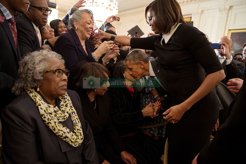 """President Barack Obama kisses the cheek of Ms. Mattie Atkins as he and First Lady Michelle Obama greet audience members during a reception celebrating Black History Month in the East Room of the White House, Feb. 26, 2015. Ms. Atkins was a """"foot soldier"""" in the civil rights marches in Marion, Ala. in 1965. (Official White House Photo by Pete Souza)<br /> <br /> This official White House photograph is being made available only for publication by news organizations and/or for personal use printing by the subject(s) of the photograph. The photograph may not be manipulated in any way and may not be used in commercial or political materials, advertisements, emails, products, promotions that in any way suggests approval or endorsement of the President, the First Family, or the White House."""