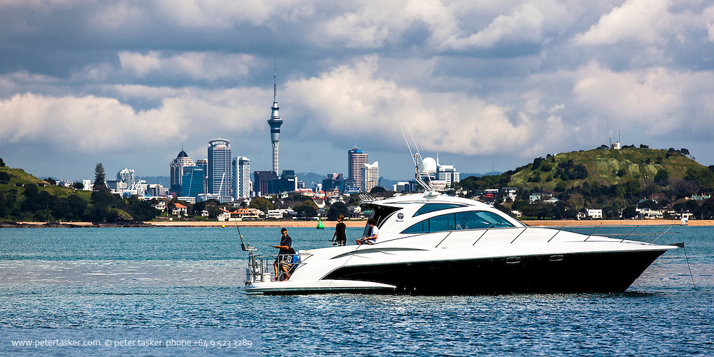 Luxury launch at anchor off Cheltenham Beach with a man and three boys fishing.  Downtown Auckland visible in gap between North Head and Mount Victoria.