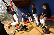 Adam Jones, age 7, right, sits in the dugout with his little league teammates in Toms River, NJ.     <br /> Adam Jones, age 7, and Jeffrey Jones, age 9, are two brothers out of 6 siblings that have different forms of autism . Their family integrates them into all forms of daily life, which include little league, physical therapy, private tutoring sessions and family meals. Every year it costs around $50,000 per child to get them the help they need to become more socialized.