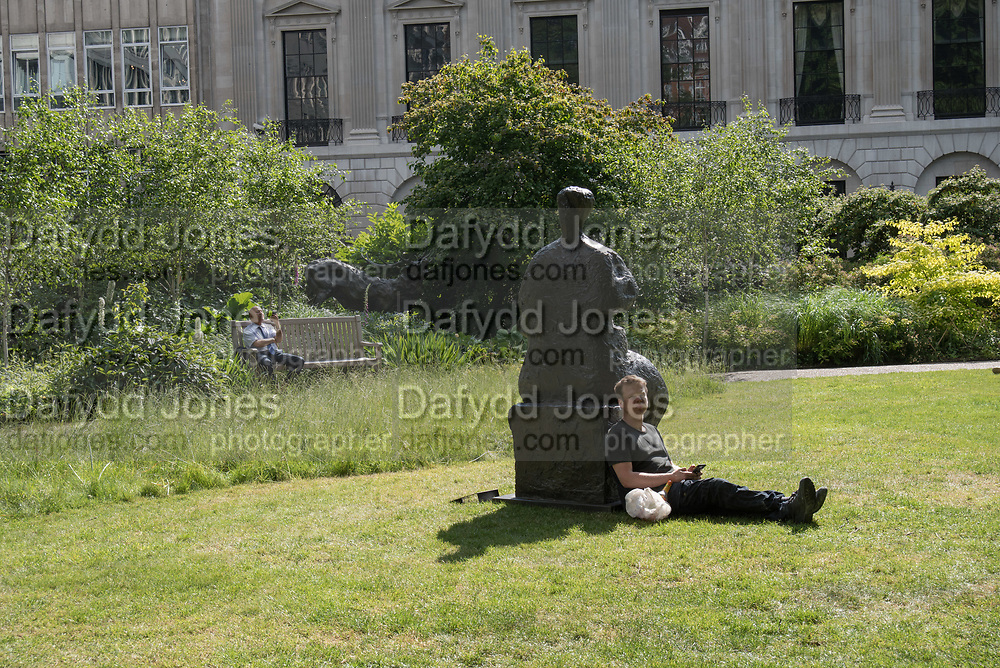 Man leaning against, ' Seated Woman' by Henry Moore, Sculpture in the park,  from an upcoming auction at Christies, St. James's Sq.park  London. 24 May 2017