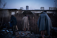 Migrant wrapped in wool blankets changing their cloths after washing themselfs outside in a makeshift camp in Belgrade, Serbia. 15th January 2017. Federico Scoppa