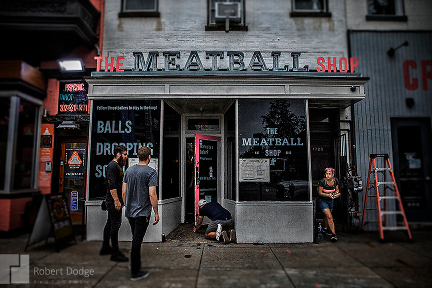 """Workers put the finishing touches on this Meatball Shop before its opening on 14th Street in Washington DC. A dapper dandy makes his way up the street from grocery shopping -- perhaps eager to taste the goodies he just purchased. This image is from Robert Dodge """"Project: 14th and U Streets,"""" a look at the center of town in Washington, D.C. For info on publication or fine-art-, limited-edition prints, contact: Robert@RobertDodge.com."""