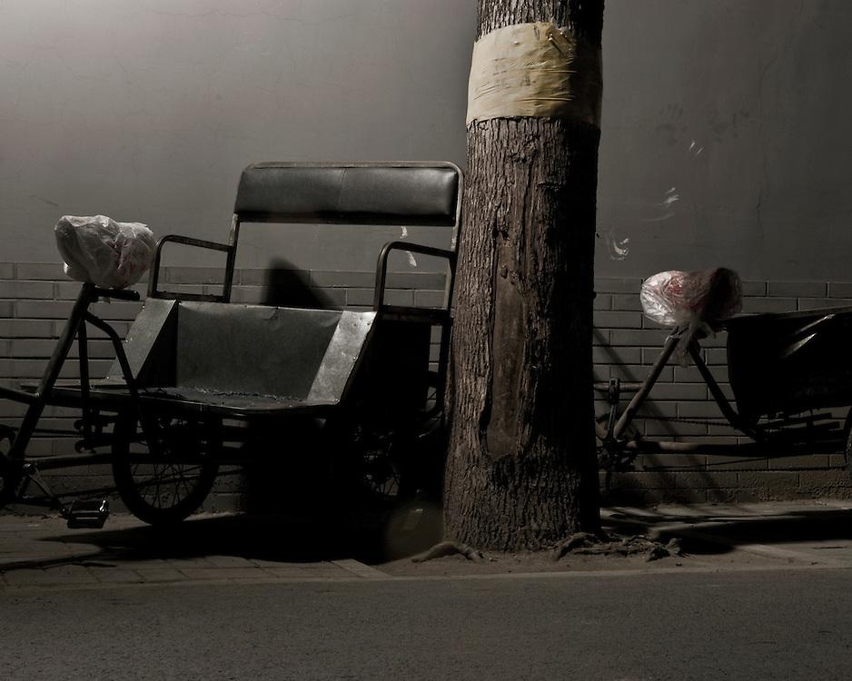Parked Rickshaw by Tree Trunk at night