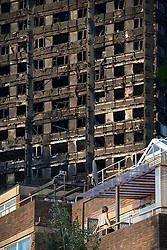 © Licensed to London News Pictures. 16/06/2017. London, UK. A woman looks from her flat up to the burnt remains of Grenfell Tower. The blaze engulfed the 27-storey building in the early hours of June 13th. Police say 30 people have been killed with 34 still in hospital, 18 of whom are in critical condition. The fire brigade say that they don't expect to find anyone else alive. Photo credit: Peter Macdiarmid/LNP
