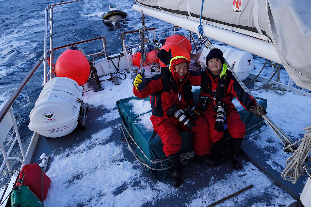 Whale watching and photography visitors/ecotourists from China on boat outside Senja, Troms county, Norway, Scandinavia