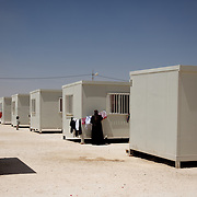 August 09, 2013 - Zarqa, Jordan: A syrian refugee is seen hanging laundry outside a portacabin at the Mrigb Al-Fuhud refugee camp, also known as Emirates-Jordanian camp, 20 kilometres east of the Jordanian city of Zarqa.<br /> The 10 million USD camp, which has 750 caravans, a hospital, and a school and can take up to four thousand people, first opened in April 2013 and was paid for by the United Arab Emirates. Work is underway to house a total of 20 thousand by the end of the year.<br /> In contrast with the two other camps in the area, Mrigb Al-Fuhud as been classified by many as a 'five star' camp due to impressive housing facilities provided to the refugees. (Paulo Nunes dos Santos/Al Jazeera)