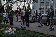 "Krasnoarmisk, Ukraine - May 11, 2014: A pro-Russian demonstrator lies dead on the grass as a group continues arguing with armed pro-Ukrainian militiamen of ""Dnepr Brigade"" from Dnepropetrovsk, in front of the administrative building in central Krasnoarmisk, some 75 kilometers northwest of Donetsk, eastern Ukraine. One pro-Russian demonstrator died and another, seriously injuried, was evacuated after being shot in the chest while throwing stones towards ""Dnepr Brigade"" members. CREDIT: Photo by Mauricio Lima for The New York Times"