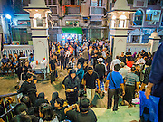 04 NOVEMBER 2014 - YANGON, MYANMAR:  People walk into Mogul Mosque (Masjid) in Yangon for Ashura services. Ashura commemorates the death of Hussein ibn Ali, the grandson of the Prophet Muhammed, in the 7th century. Hussein ibn Ali is considered by Shia Muslims to be the third imam and the rightful successor of Muhammed. He was killed at the Battle of Karbala in 610 CE on the 10th day of Muharram, the first month of the Islamic calendar. According to Myanmar government statistics, only about 4% of the population is Muslim. Many Muslims have fled Myanmar in recent years because of violence directed against Burmese Muslims by Buddhist nationalists.   PHOTO BY JACK KURTZ