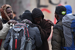 © Licensed to London News Pictures. 24/10/2016. Calais, France. An African migrant cries as he says goodbye to a friend as they are separated while leaving the Jungle. Evacuation and demolition begins at the migrant camp in Calais, known as the 'Jungle'. French authorities have given an eviction order to thousands of refugees and migrants living at the makeshift living area of the French coast. Photo credit: Ben Cawthra/LNP