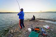Spanje, El Ejido, 6-11-2019  Arbeidsmigranten uit Oost-europa, Bulgarije in dit geval, vissen in een klein meertje in het kassengebied . Ze gaan ze eten en niet teruggooien.Foto: Flip Franssen