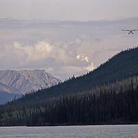 Logan Mountains, Northwest Territories, Canada.A float plane approaches Glacier Lake.