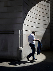 © Licensed to London News Pictures. 25/06/2018. London, UK. A city workers holds his jacket as he  passes through a circle of sunlight formed at the corner of the Bank of England as high temperatures remain in most of the UK. Photo credit: Peter Macdiarmid/LNP