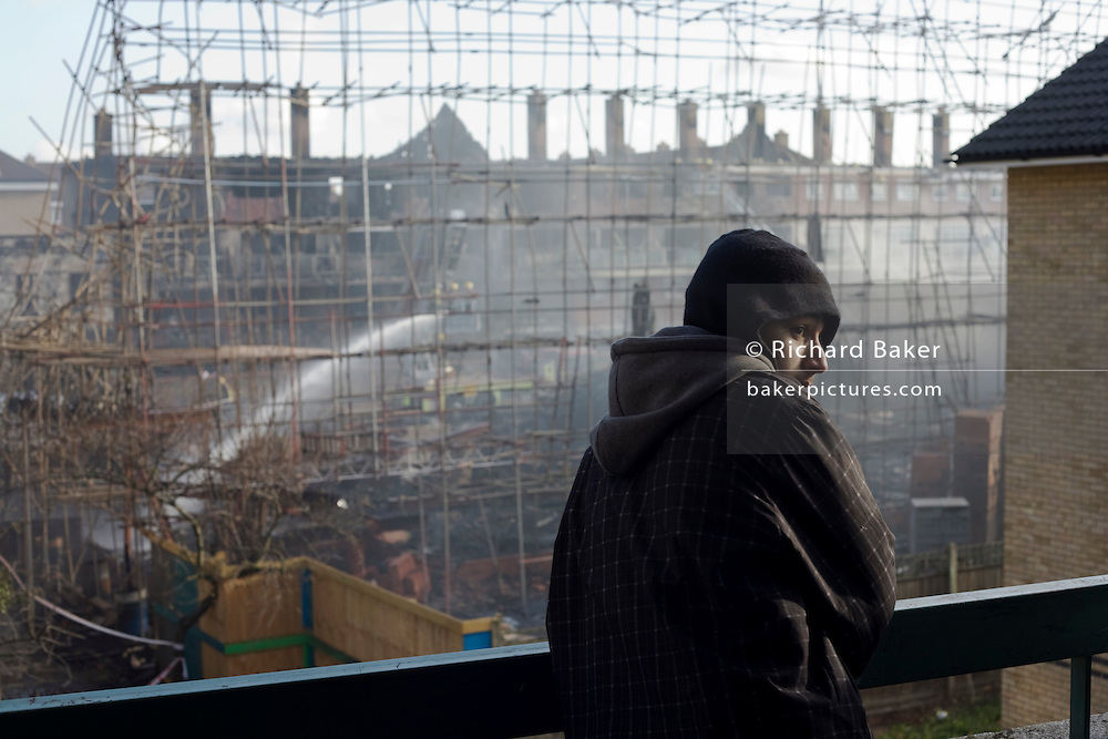 Young hoodie looks at the devastation of a construction site after an inner-city estate fire in south London. About 310 people were forced to leave their homes after the fire engulfed a wooden structure under construction in scaffolding at Sumner Road and Garrisbrooke Estate, Peckham, London at about 0430 AM. It spread to two blocks of maisonettes and a destroyed a pub. More than 150 firefighters tackled this unusually large and ferocious fire which injured ten people, including two police officers who received hospital treatment for minor injuries.  .