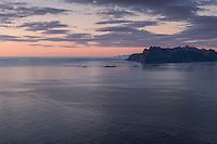 Summer twilight over sea and distant mountains of Vestvågøy from summit of Hornet, Flakstadøy, Lofoten Islands, Norway