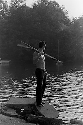 muscular man holding oars by a lake
