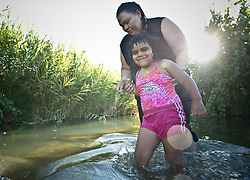 Surita Hernandez brings her daughter Ayashe, 4, into the wate to swim in a river on the Moapa reservation outside Las Vegas, Nevada in July, 2012. They don't get to go outside as often as they like because of the poor air quality.   All of their family suffers from Asthma and though they can't prove it, believe its because of the coal plant next door. Her grandfather died in march because of cancer. The Sierra Club is working with the Moapa Band of Paiutes to transition NV Energy away from the Reid Gardner coal-fired power plant -- which sits only 45 miles from Las Vegas and a short walk from community housing at the Moapa River Indian Reservation. The Reid Gardner coal plant is literally spewing out tons of airborne pollutants such as mercury, nitrous oxide, sulfur dioxide, and greenhouse gases. This has resulted in substantial health impacts on the Moapa community, with a majority of tribal members reporting a sinus or respiratory ailment. Vernon Lee believes that the many people on the Moapa reservation suffering from health issues are because of the coal plant next door. Sierra Club is working with the Moapa Band of Paiutes to transition NV Energy away from the Reid Gardner coal-fired power plant -- which sits only 45 miles from Las Vegas and a short walk from community housing at the Moapa River Indian Reservation. The Reid Gardner coal plant is literally spewing out tons of airborne pollutants such as mercury, nitrous oxide, sulfur dioxide, and greenhouse gases. This has resulted in substantial health impacts on the Moapa community, with a majority of tribal members reporting a sinus or respiratory ailment.