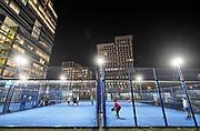 Nederland, Amsterdam, 16-1-2020 Beeld van de zuidas ter hoogte van station Zuid en WTC . Jonge werknemers van de kantoren sporten op het tennisveld wat tussen de hoogbouw ligt .Sport, bewegen,tennis,sportveld .World trade center, zuidplein , gustav mahlerplein,  . Foto: Flip Franssen