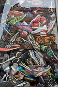 A detail of old trainers are stacked in the window of a sports accessories shop, on Milady Horakove street, Holesovice district, Prague 7, on 18th March, 2018, in Prague, the Czech Republic.