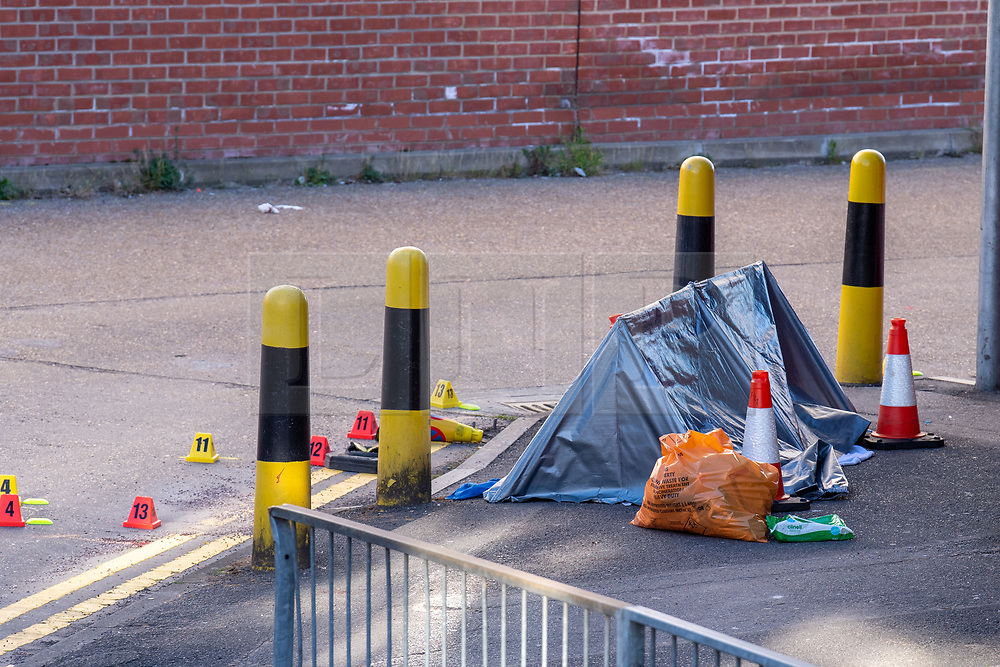 © Licensed to London News Pictures. 22/04/2021. Walton-on-Thames, UK. A forensic tent covers what appears to be a body at the scene behind a row of shops. Police responded to an incident at 14:15 BST on Church Street in Walton-on-Thames, police and forensic investigators could be seen at the scene. Photo credit: Peter Manning/LNP