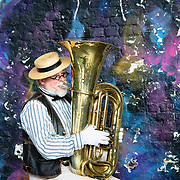 Man playing a tuba in front of graffitied wall