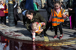 London, UK. 9th March, 2019. A young child dips her finger in artificial blood poured by climate activists from Extinction Rebellion on the ground outside Downing Street as part of an act of civil disobedience named 'The Blood of Our Children' to call on the Government to take immediate steps to combat the current climate and ecological emergency.