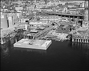 """Ackroyd 11179-1. """"aerial Albina Engine & Machine Works. Barge DeLong. October 1, 1962"""" (The DeLong corporation was involved in the construction of the Columbia River bridge at Astoria.)"""