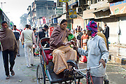 Indian woman shopping by rickshaw in Old Delhi at Daryagang fruit and vegetable market, India