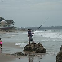A fisherman and his daughter enjoy the Pacific Ocean at Zuma Beach by Malibu, California.