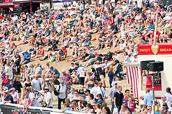 © Licensed to London News Pictures. 26/07/2018. Llanelwedd, Powys, UK. Visitors on the burnt 'Grassy Knoll' watch the Parade of Champions take place in the Main Ring on the last day of the Royal Welsh Agricultural Show. The Royal Welsh Agricultural Show is hailed as the largest & most prestigious event of its kind in Europe. In excess of 200,000 visitors are expected this week over the four day show period. The first ever show was at Aberystwyth in 1904 and attracted 442 livestock entries. Photo credit: Graham M. Lawrence/LNP