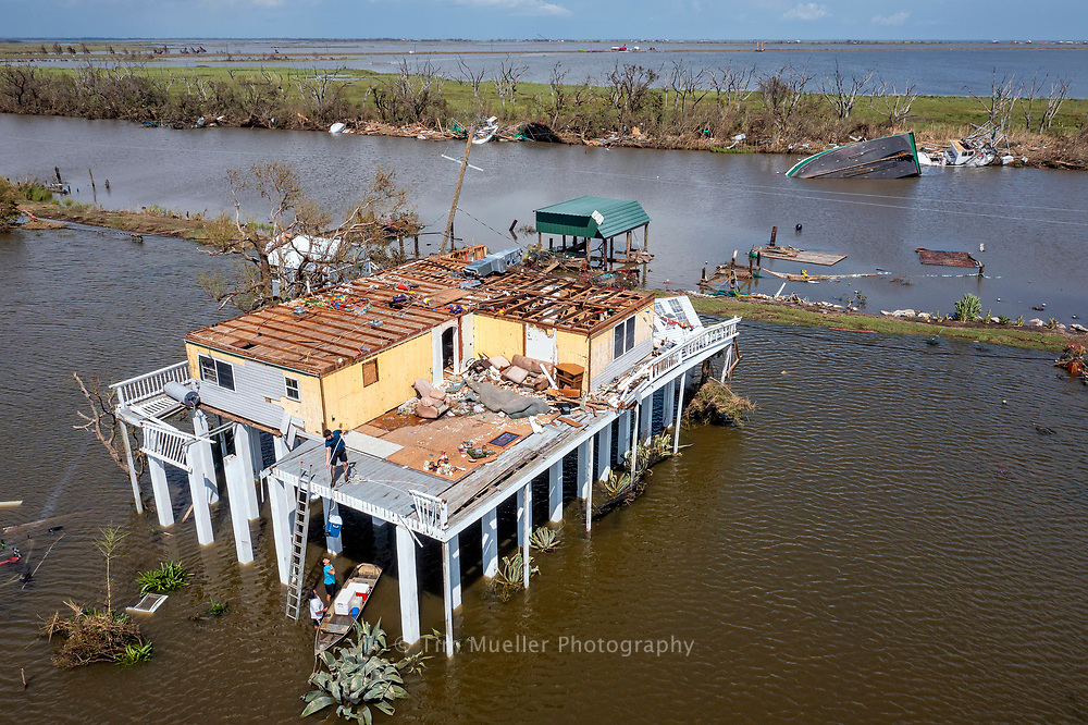 Shrimper Kim Guy, bottom left, delivers ice to his wind damaged home south of Chauvin, La. Catagory 4 Hurricane Ida passed through Terrebonne Parish with winds up to 150 mph damaging business and homes throughout the parish.
