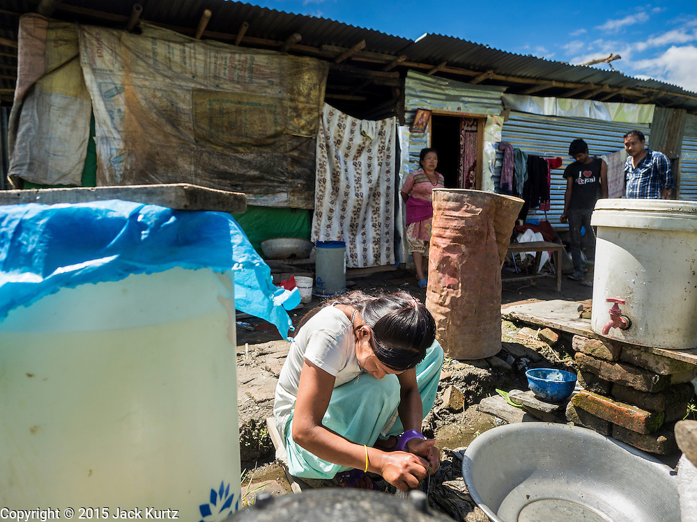 03 AUGUST 2015 - SANKHU, NEPAL:  A woman does her dishes near their temporary housing in a rice field in Sankhu, a community about 90 minutes from central Kathmandu. Her home was destroyed in the earthquake. The Nepal Earthquake on April 25, 2015, (also known as the Gorkha earthquake) killed more than 9,000 people and injured more than 23,000. It had a magnitude of 7.8. The epicenter was east of the district of Lamjung, and its hypocenter was at a depth of approximately 15km (9.3mi). It was the worst natural disaster to strike Nepal since the 1934 Nepal–Bihar earthquake. The earthquake triggered an avalanche on Mount Everest, killing at least 19. The earthquake also set off an avalanche in the Langtang valley, where 250 people were reported missing. Hundreds of thousands of people were made homeless with entire villages flattened across many districts of the country. Centuries-old buildings were destroyed at UNESCO World Heritage sites in the Kathmandu Valley, including some at the Kathmandu Durbar Square, the Patan Durbar Squar, the Bhaktapur Durbar Square, the Changu Narayan Temple and the Swayambhunath Stupa. Geophysicists and other experts had warned for decades that Nepal was vulnerable to a deadly earthquake, particularly because of its geology, urbanization, and architecture.    PHOTO BY JACK KURTZ