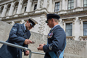 On the 100th anniversary of the Royal Air Force (RAF) and following a flypast of 100 aircraft formations representing Britain's air defence history which flew over central London, a senior officer shows his pass to enter Horseguards, next to the memorial to those killed in the 2002 Bali bombing, on 10th July 2018, in London, England.