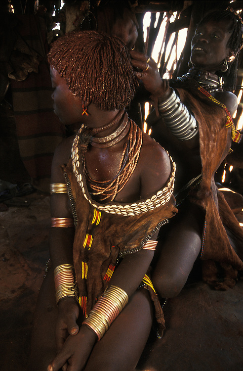 A female member of her fiancé's family applies red ochre and butter to a bride-to-be's hair, shoulders and chest at a Hamar couple's betrothal ceremony, in South Omo, Ethiopia. The 40,000-strong, cattle-herding Hamar are among the largest of the 20 or so ethnic groups which inhabit the culturally diverse South Omo region in south-west Ethiopia.