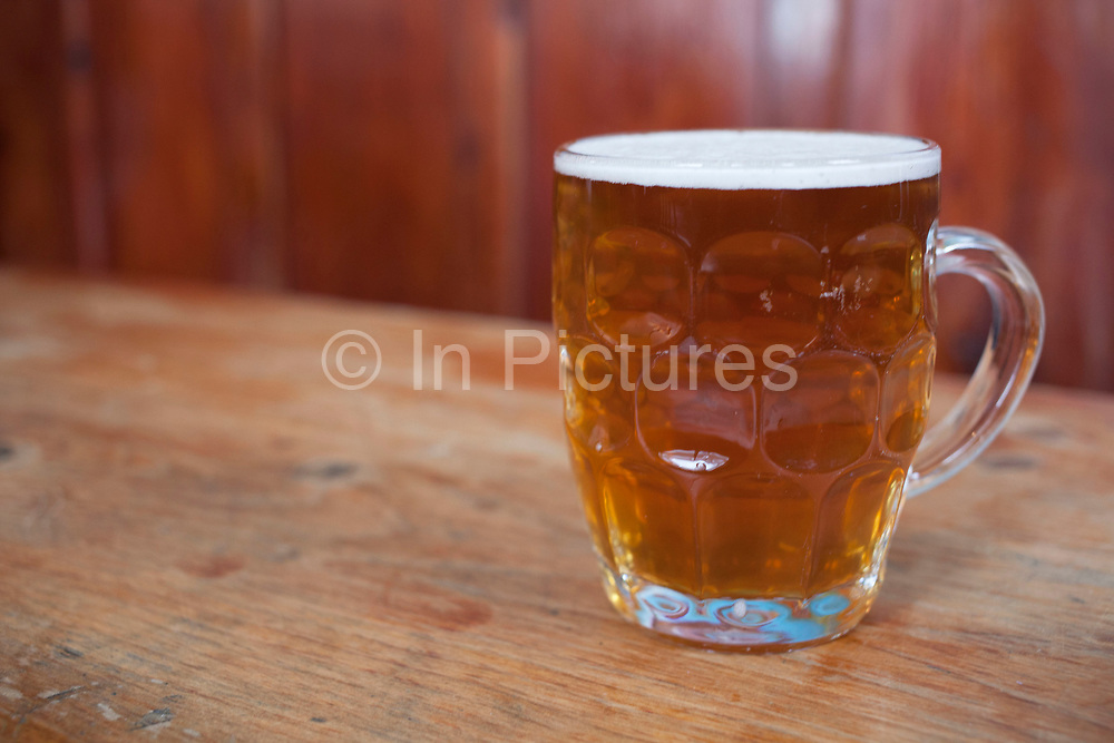 """Pint of ale in an old fashioned jug beer glass. Jug glasses are shaped more like a large mug with a handle. They are moulded with a grid pattern of thickened glass on the outside. Dimpled glasses are now rarer than the other types and are regarded as more traditional. This sort of glass is also known as a """"Handle"""" or """"Jug"""". They are popular with drinkers who prefer a traditional beer experience."""
