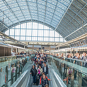 Passengers disembark and use a moving walkway under the distinctive iron and glass arched cover over the platforms of St Pancras Railway Station (now known as St Pancras International). The renovated station features distinctive Victorian architecture and serves as a Eurostar terminal for high-speed trains to Europe. There are also platforms for domestic train services. The distinctive train shed roof was designed by William Henry Barlow.