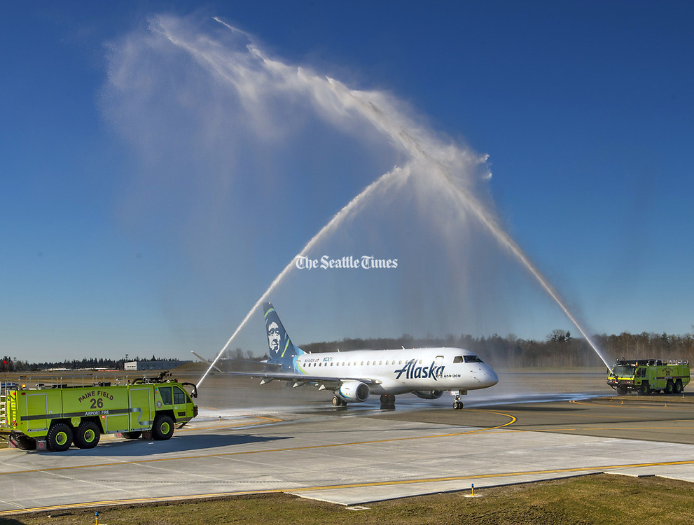 The Paine Field Fire Department creates a water arch salute over flight 2878 to Portland. This Embraer 175, operated by Alaska's Horizon Airlines, is the first passenger-service flight from Everett's Paine Field. (Mike Siegel / The Seattle Times)