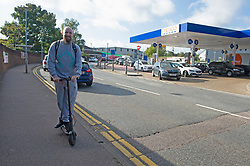 © Licensed to London News Pictures 24/09/2021.<br /> Sidcup, UK, This man is all smiles on his electric scooter as cars queue. Motorists queuing for up to an hour at Tesco Petrol station in Sidcup, South East London. Chaos at the forecourts as people start to panic buy petrol. BP has started to ration petrol and diesel due to a shortage of truckers. Photo credit:Grant Falvey/LNP