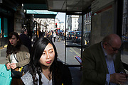 Street Scene on Piccadilly in London, England, United Kingdom. A well dressed gentleman in a tweed jacket waits at a bus stop in the sunshine while young Chinese girls pass.